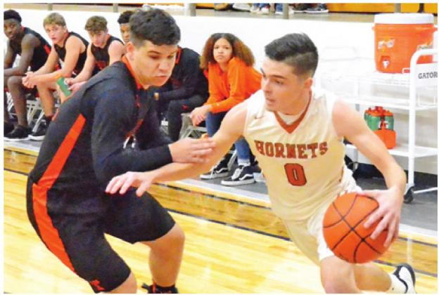 BOBBY LAROUAX DRIBBLES the ball past this Smithville defender on Friday, Jan. 17, in Caldwell. The Hornets won their district opener 60-38. -- Tribune photo by Roy Sanders