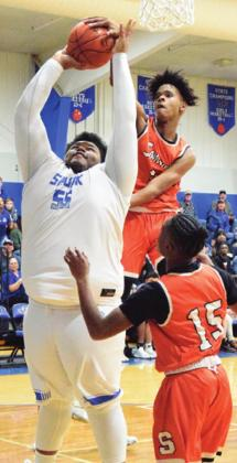 DOMINIC TUCKER blocks a shot by Snook's James Young during their game last Tuesday night. -- Tribune photo by Denise Hornaday
