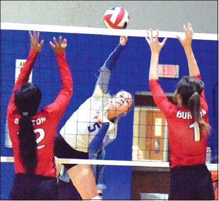 SNOOK'S KENZIE KMIEC hits the ball between Burton's Azhane Graves and Alex Countouriotis during the Lady Jays' win over Burton on Tuesday, Oct. 1. -- Tribune photo by Denise Hornaday