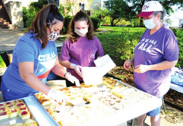 AIMEE MARKERT SERVES these kolaches to Beth Campbell of Dime Box during the second Saturday celebration in downtown Caldwell.