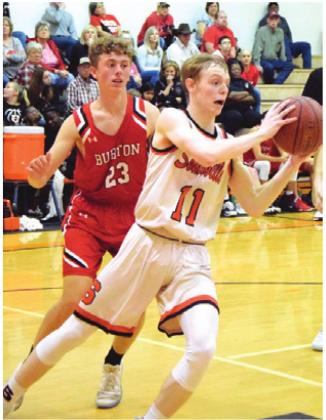 GARRISON BALLARD gets around a Burton defender at the baseline to pass the ball to a teammate during Friday night's home game.